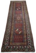 AN OLD PERSIAN POLYCHROME RUNNER with central alternating panels of botehs and stylised birds within