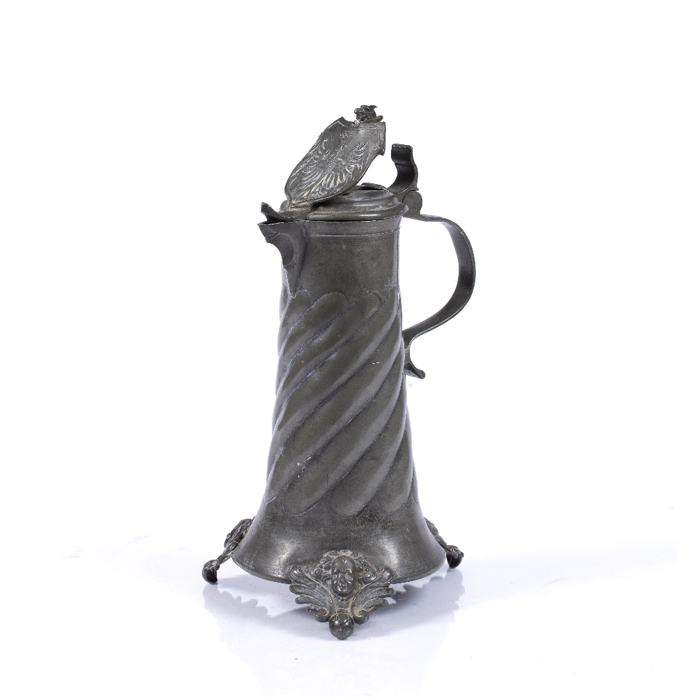 A GERMAN PEWTER FLAGON the hinged lid with heraldic crest, scroll handle, wrythen and wrigglework