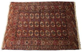 A TEKKE BOKHARA MID RED GROUND TRIBAL RUG decorated three rows of nine elephant foot medallions