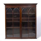 A GEORGE III MAHOGANY BOOKCASE, the top with moulded cornice above two lancet astragal glazed