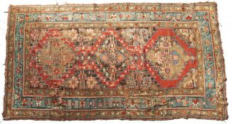 A CAUCASIAN RUG with triple medallion filled with florettes, wild beasts and formal designs, with
