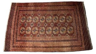 A TEKKE BOKHARA RED GROUND TRIBAL RUG decorated two rows of eight elephant foot medallions with a