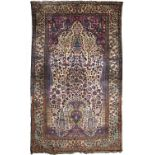 AN ANTIQUE PERSIAN KASHAN SILK RUG finely decorated with a central vase of polychrome flowers with
