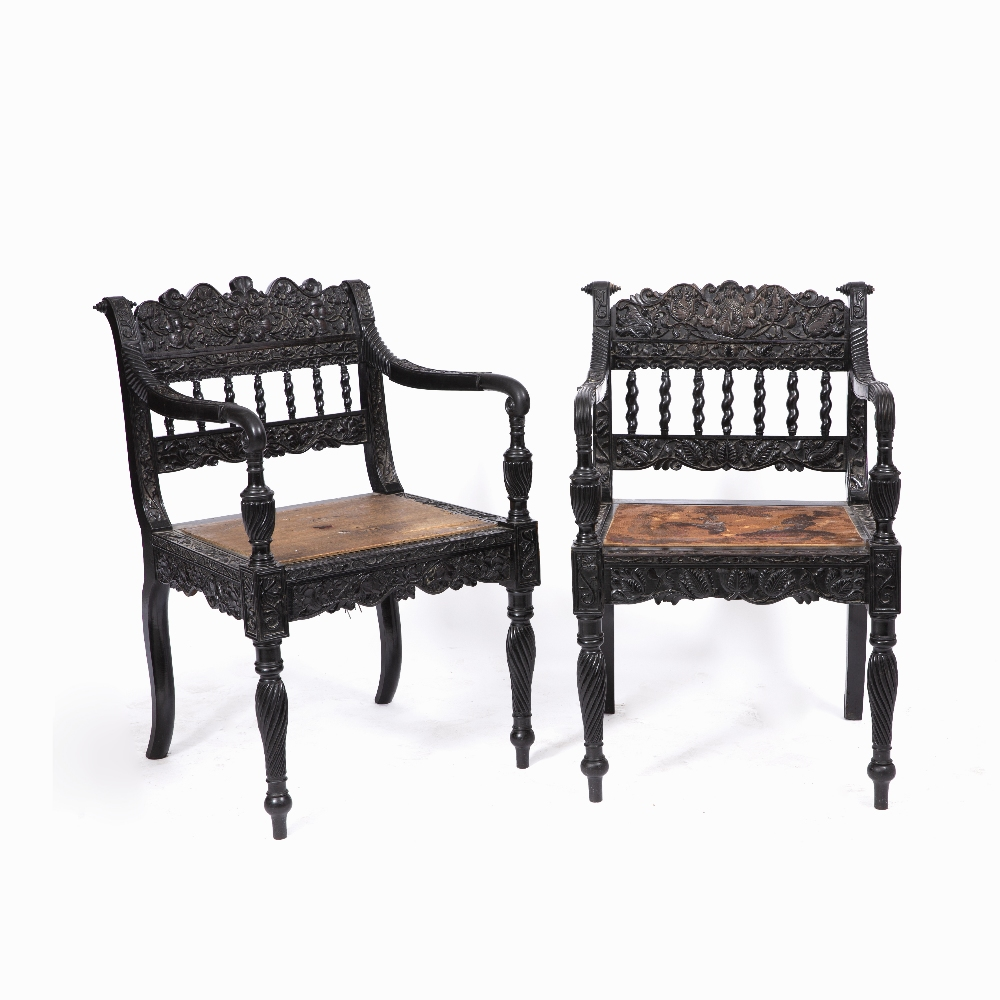 A NEAR PAIR OF EARLY 19TH CENTURY CEYLONESE CARVED EBONY OPEN ARMCHAIRS the foliate crest rails over