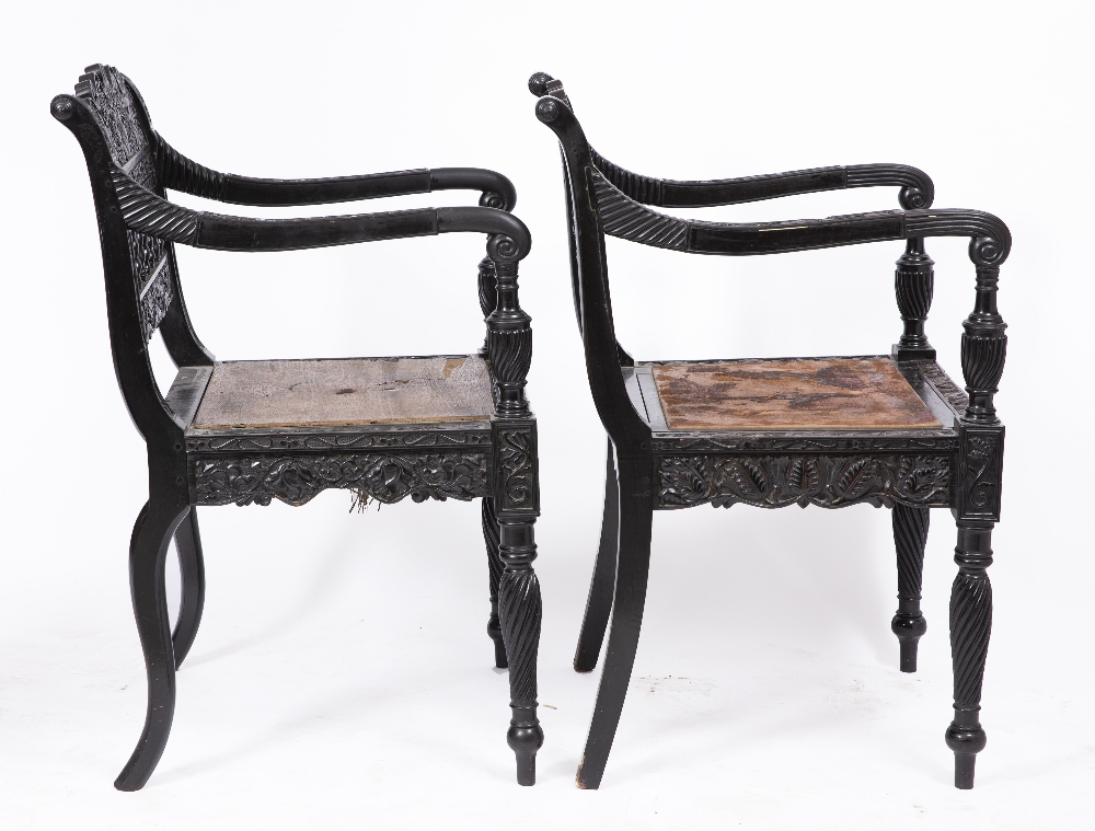 A NEAR PAIR OF EARLY 19TH CENTURY CEYLONESE CARVED EBONY OPEN ARMCHAIRS the foliate crest rails over - Image 5 of 8