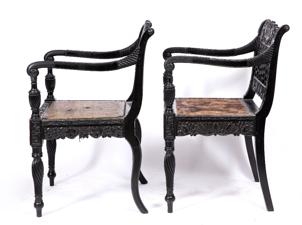 A NEAR PAIR OF EARLY 19TH CENTURY CEYLONESE CARVED EBONY OPEN ARMCHAIRS the foliate crest rails over - Image 3 of 8