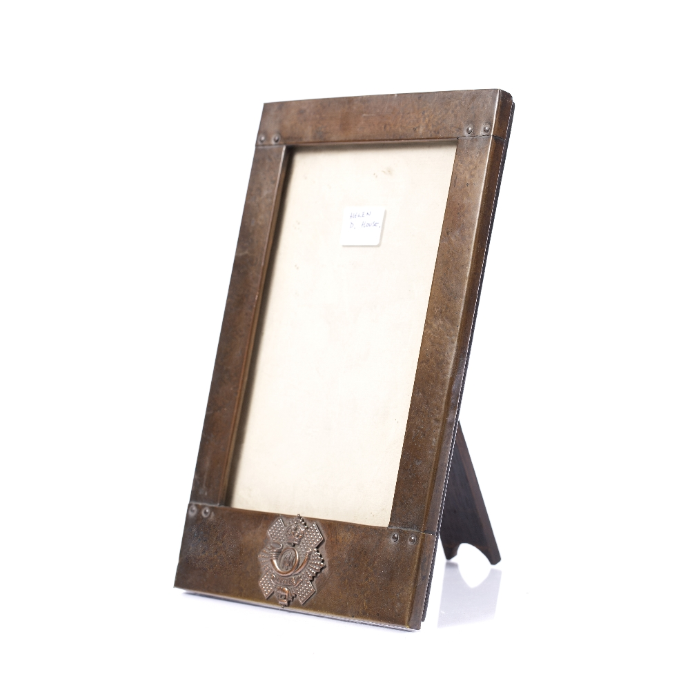 AN ARTS & CRAFTS BEATEN COPPER RECTANGULAR PHOTOGRAPH FRAME bearing the badge for the 74th