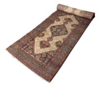 AN OLD PERSIAN HAMADAN LONG RUNNER with an interlocking hooked diamond pattern on a camel ground,