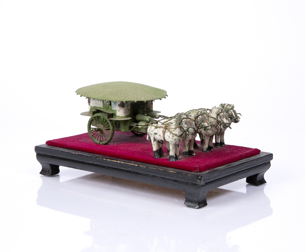 "A CHINESE MINIATURE PAINTED WOOD AND METAL FOUR HORSEDRAWN CARRIAGE mounted on a stand, 8"" long"