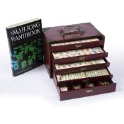 A 20TH CENTURY MAH JONG SET comprising of bone and bamboo playing pieces, contained within a five