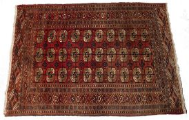 A TEKKE BOKHARA TRIBAL RUG with three rows of ten medallions on a deep red ground and within a