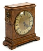 An antique clock movement with a verge escapement, mounted in a 19th century walnut case with a