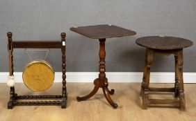 An antique oak circular topped occasional table with turned supports and pegged construction, 35cm