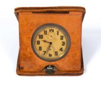 An early 20th century Longines desk timepiece in a fitted leather case and having arabic numerals,