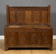 An 18th century oak and iron bound monks bench with carved panels, 116cm wide x 49cm deep x 110cm