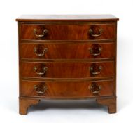 A reproduction Georgian style flame mahogany bow front chest of four long drawers with brass swan