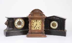 An American black mantle clock with lion mask ornament to either end; an old slate mantle clock with