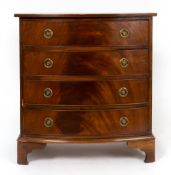A reproduction Georgian style mahogany bow front chest of four long drawers with brass ring