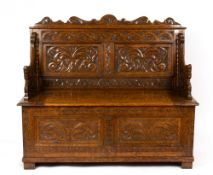 An early 20th century carved oak box settle with dragons mask arms, 121cm wide x 48cm deep x 104cm