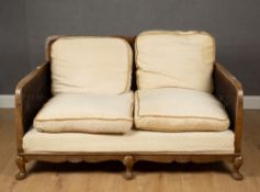A 1930's walnut framed Bergere settee with a shaped caned back and sides, 138cm wide x 81cm deep x
