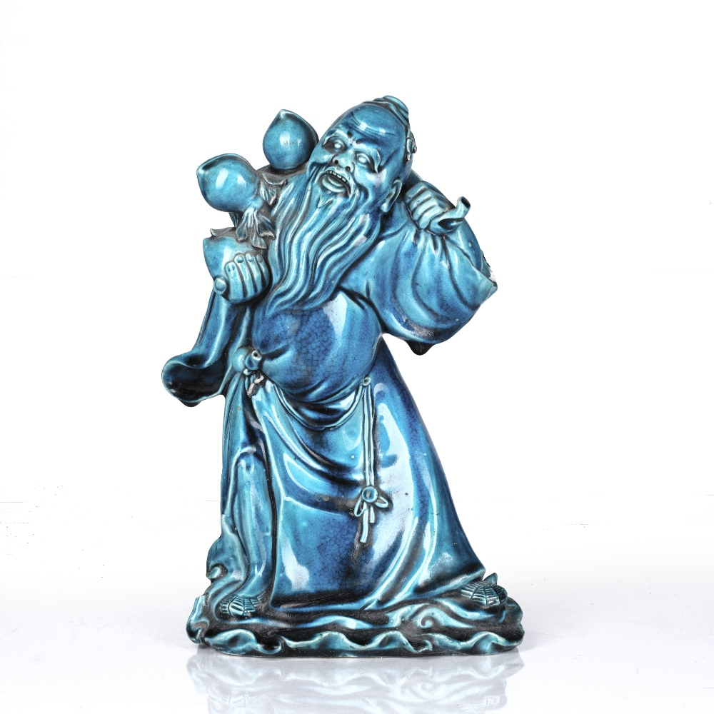 Turquoise glazed Lohan Chinese, 18th/19th Century the slightly stooped figure holding a peach in his