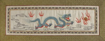 Chinese silk embroidered panel of a five clawed dragon chasing a flaming pearl, worked in coloured