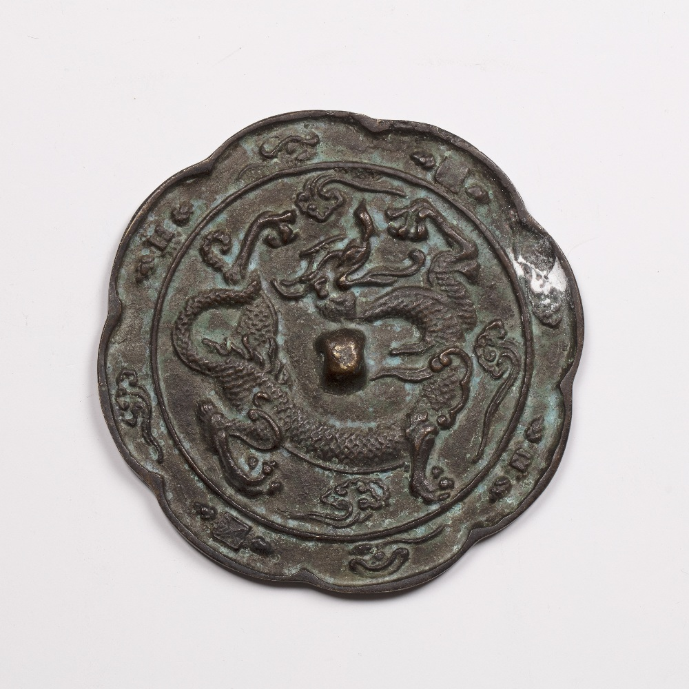 Bronze mirror Tang Dynasty of eight lobes, cast with dragon and cloud scrolls, 12.5cm diameter