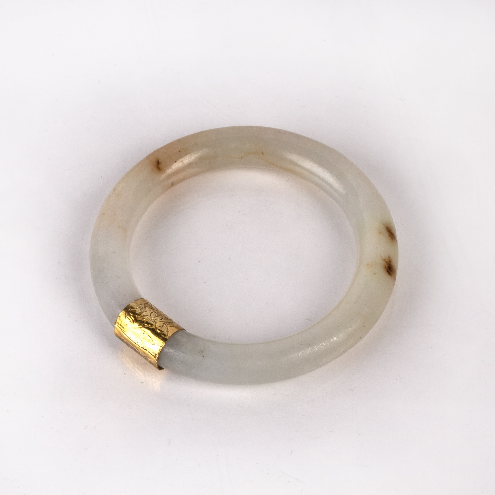 Jadeite bangle Burmese with a yellow metal mount, 7.5cm across Condition: general wear, (untested