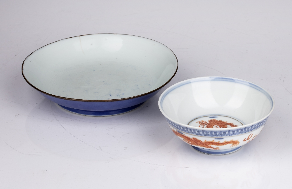 Two porcelain bowls Chinese, 18th Century and later comprising of a shallow blue glazed dish,