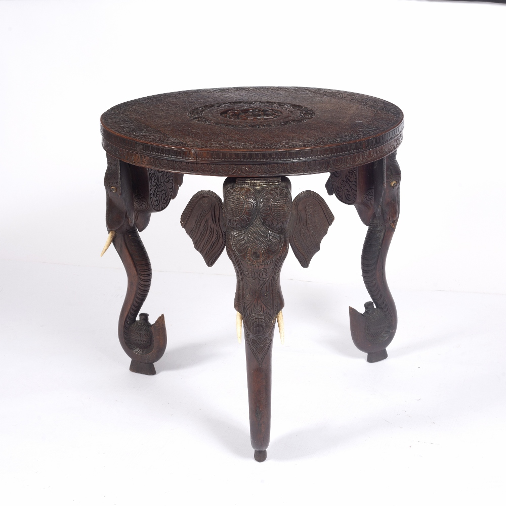 Carved hardwood circular table Indian, circa 1920/30 on carved elephant supports with ivory tusks,