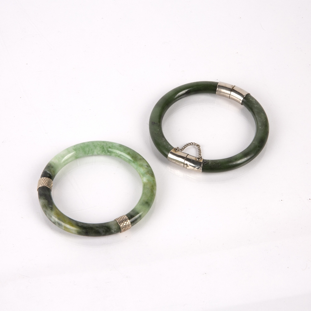 Two spinach jadeite bangles Chinese with white metal mounts, 8cm across (2) Condition: general wear, - Image 2 of 2