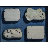 Collection of four white jade pendants Chinese, 18th Century mounted in a black and blue fitted