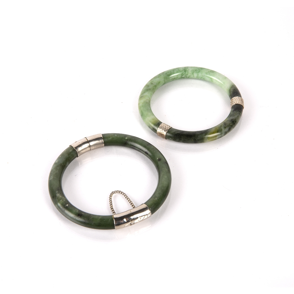 Two spinach jadeite bangles Chinese with white metal mounts, 8cm across (2) Condition: general wear,