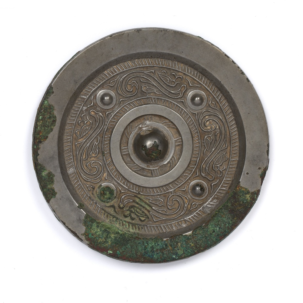 Silvered bronze circular mirror Chinese cast with a central knob surrounded by a patterned ground,