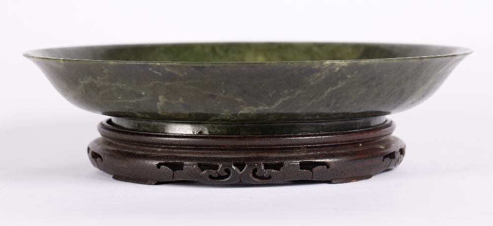 Nephrite jade shallow dish Chinese, 19th Century the dish with raised rim, on a hardwood stand, 25cm - Image 2 of 5