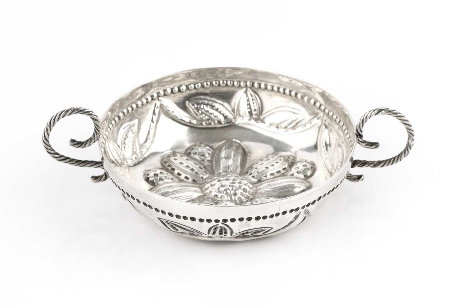 An early 20th century Britannia Standard silver taste vin, embossed with a flowerhead and foliage,