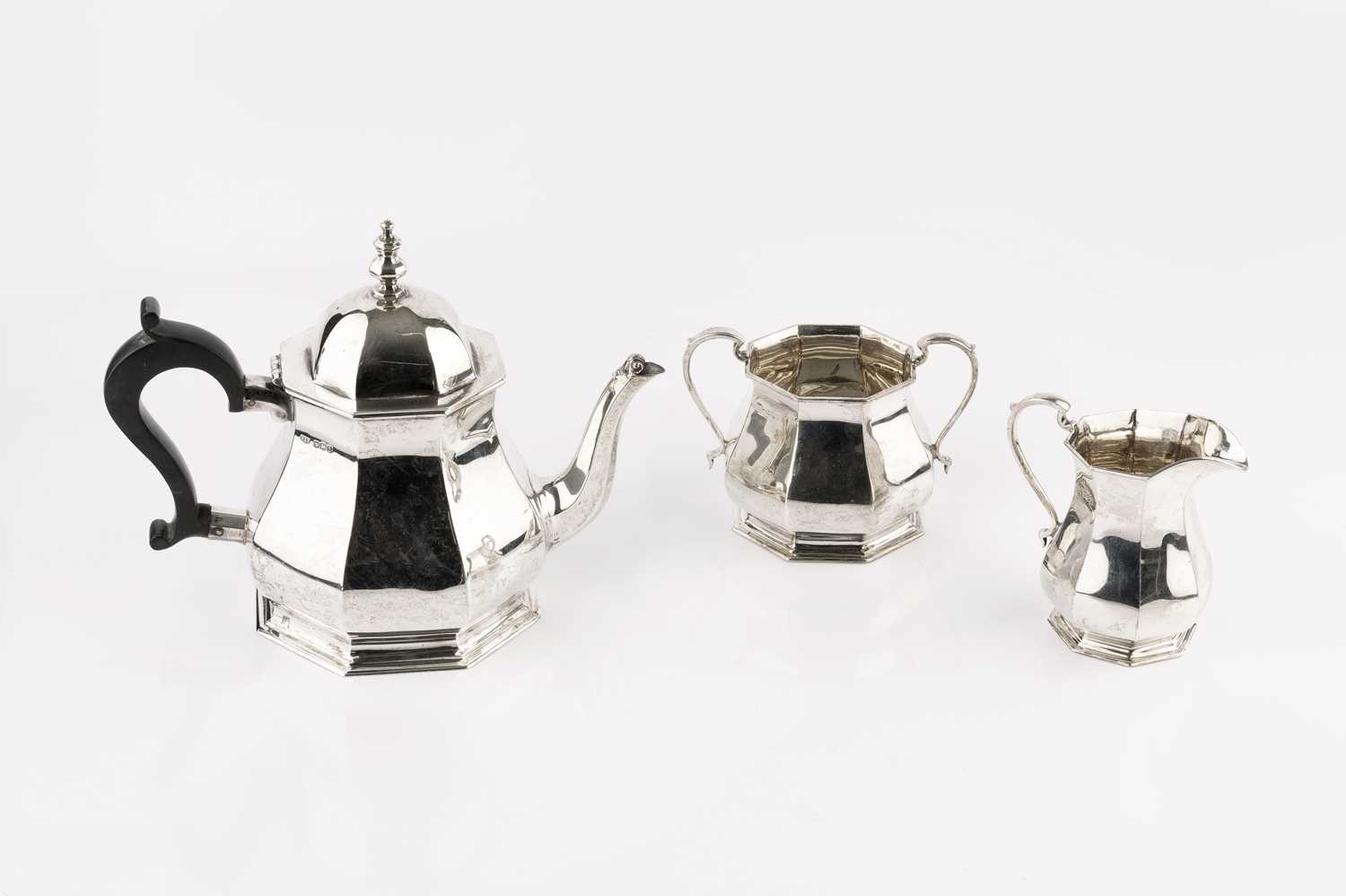 A silver three piece tea service, of octagonal baluster form, the teapot with ebonised handle, by