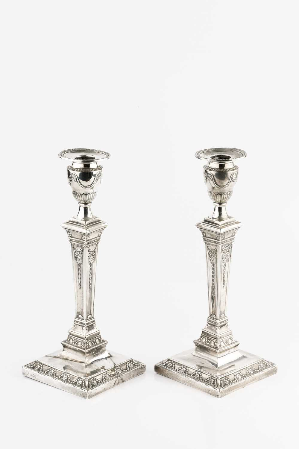 A pair of late Victorian silver candlesticks, of neo-classical design, the tapering square section