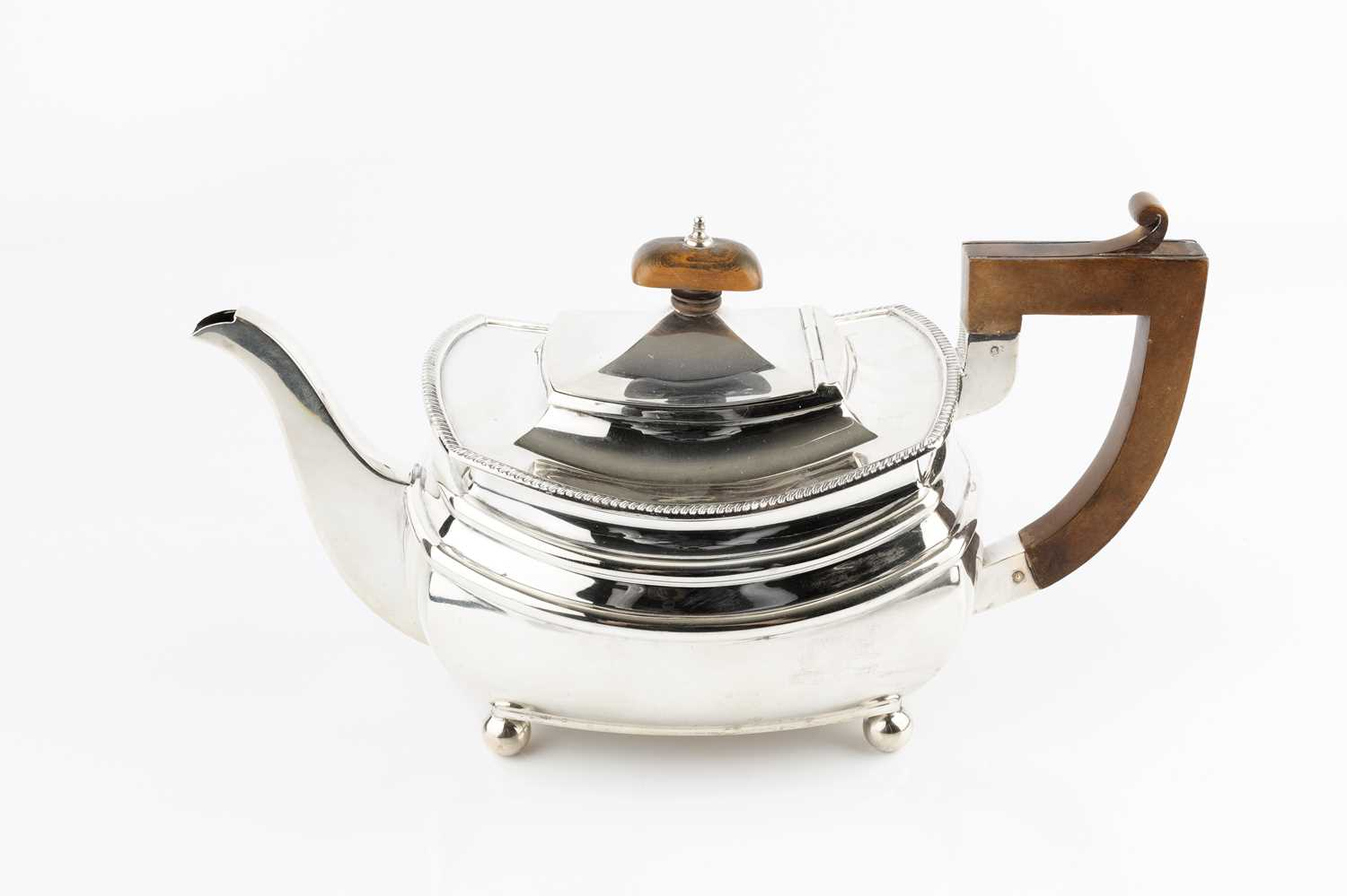 A silver teapot, with gadrooned border, composite handle and knop, on ball feet, by S