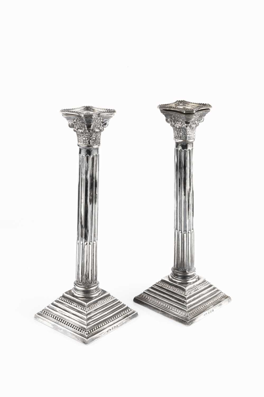 A pair of silver candlesticks, of Corinthian column form, on beaded stepped square bases, by