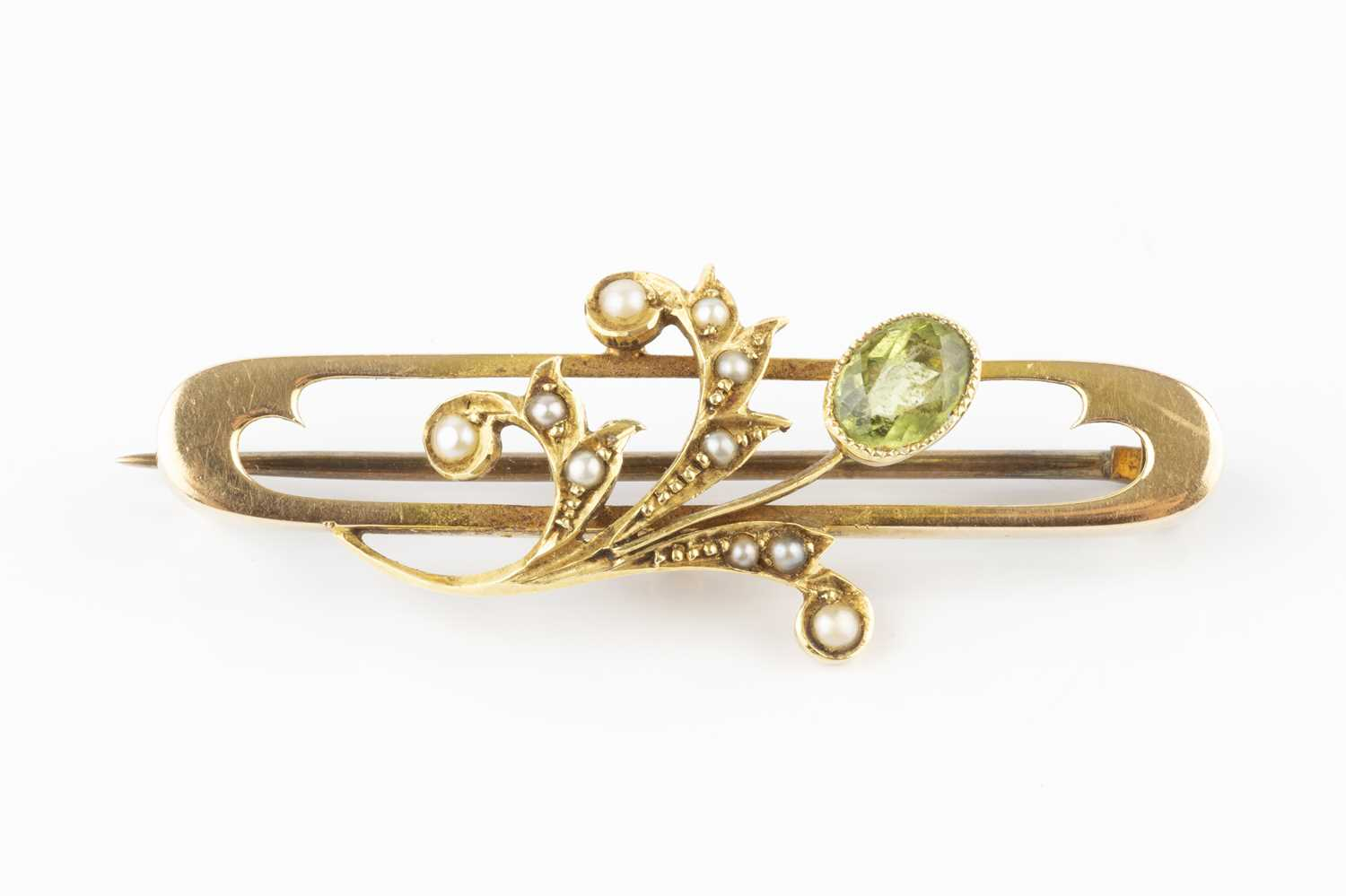 A peridot and half pearl panel brooch, the elongated oval openwork panel applied with a foliate