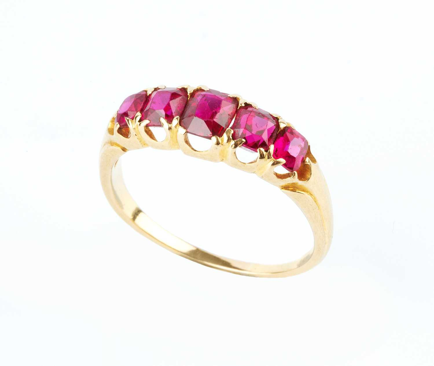 A ruby five stone ring, the graduated cushion-shaped mixed-cut rubies in fancy claw setting,