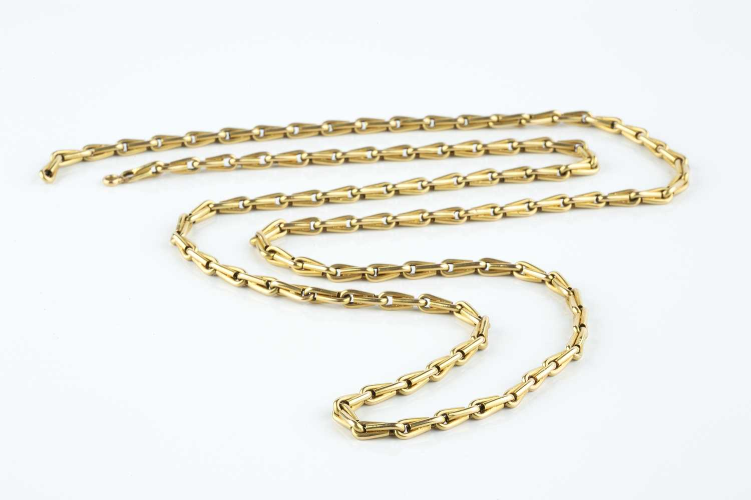 A yellow precious metal fancy-link chain, designed as a line of hollow shaped baton links, (clasp