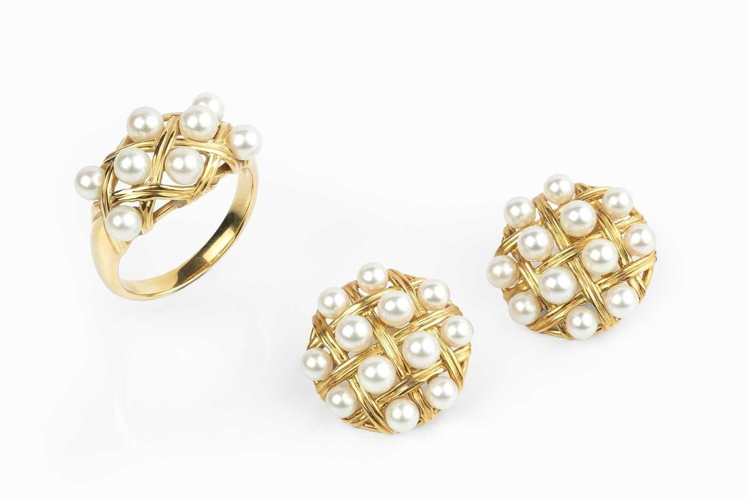 A cultured pearl ring and ear clips suite, each designed as a lattice-work panel, interspersed