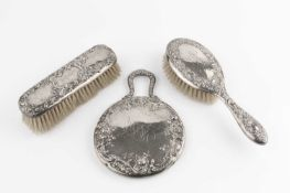 An American silver three piece dressing table set, repoussé decorated with flowers and scrolling
