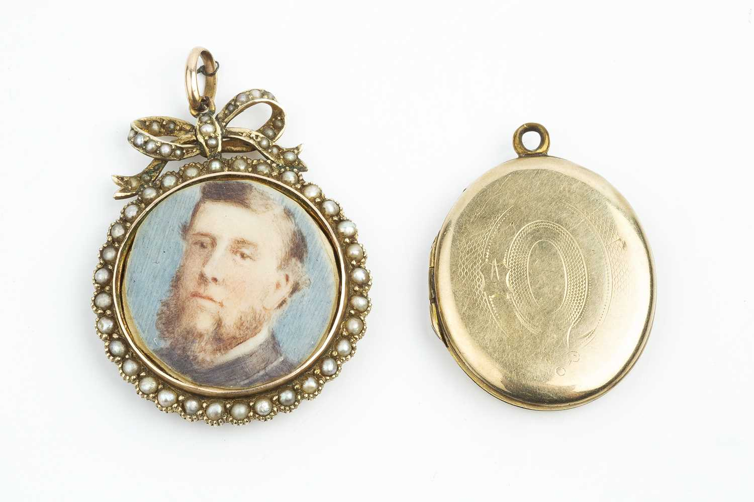 A late Victorian half pearl locket pendant, the dual-sided glazed locket containing two portrait