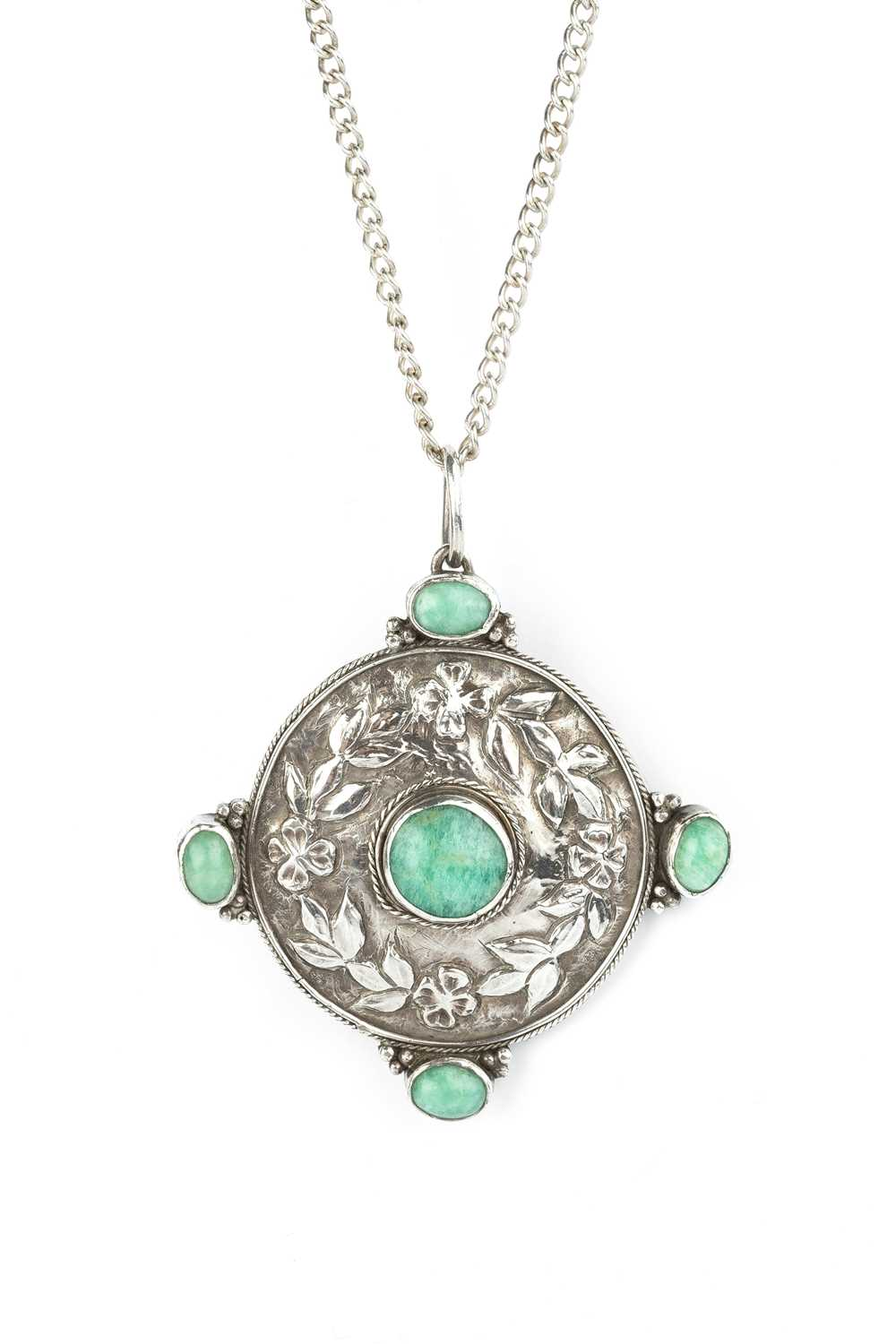 An Arts and Crafts pendant, the circular panel decorated with a wreath of foliage and flowerheads,