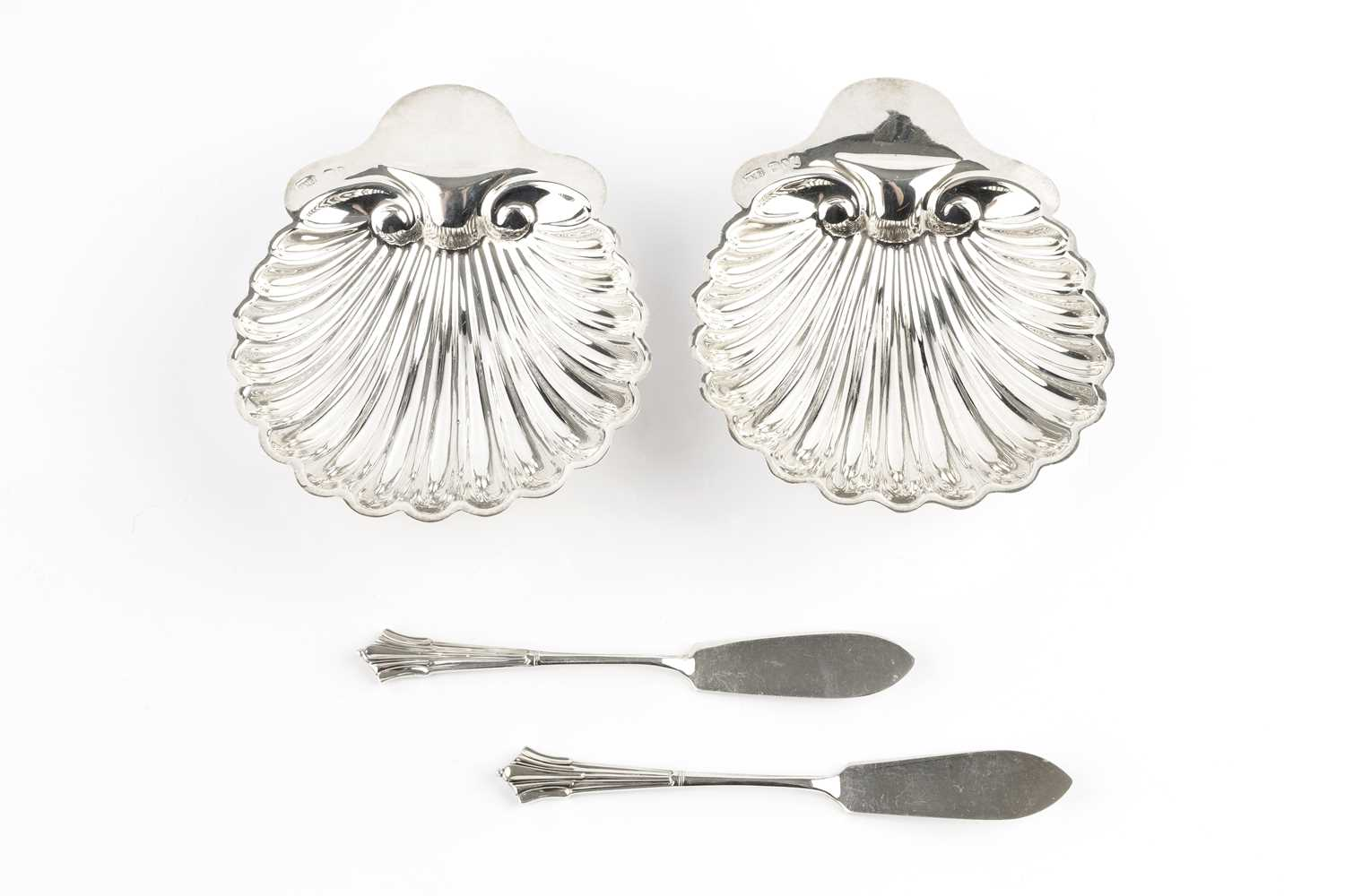 A pair of late Victorian silver butter shells, on bun feet, and with matching butter knives, by