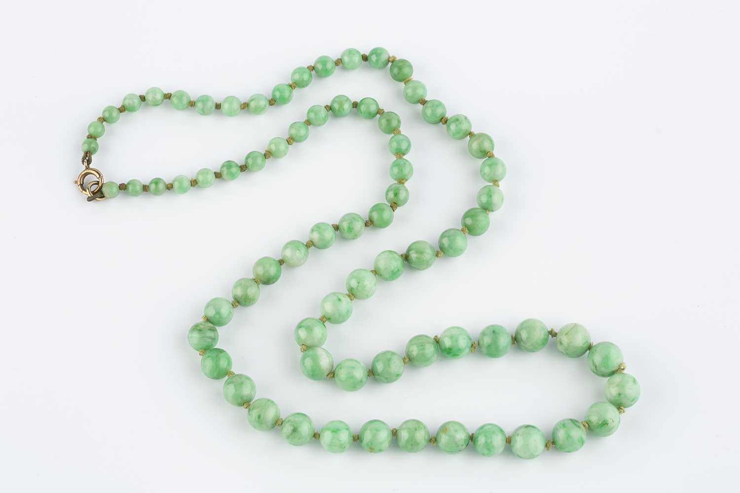 A jade bead necklace, comprising a single strand of jade beads, graduating from approximately 9.