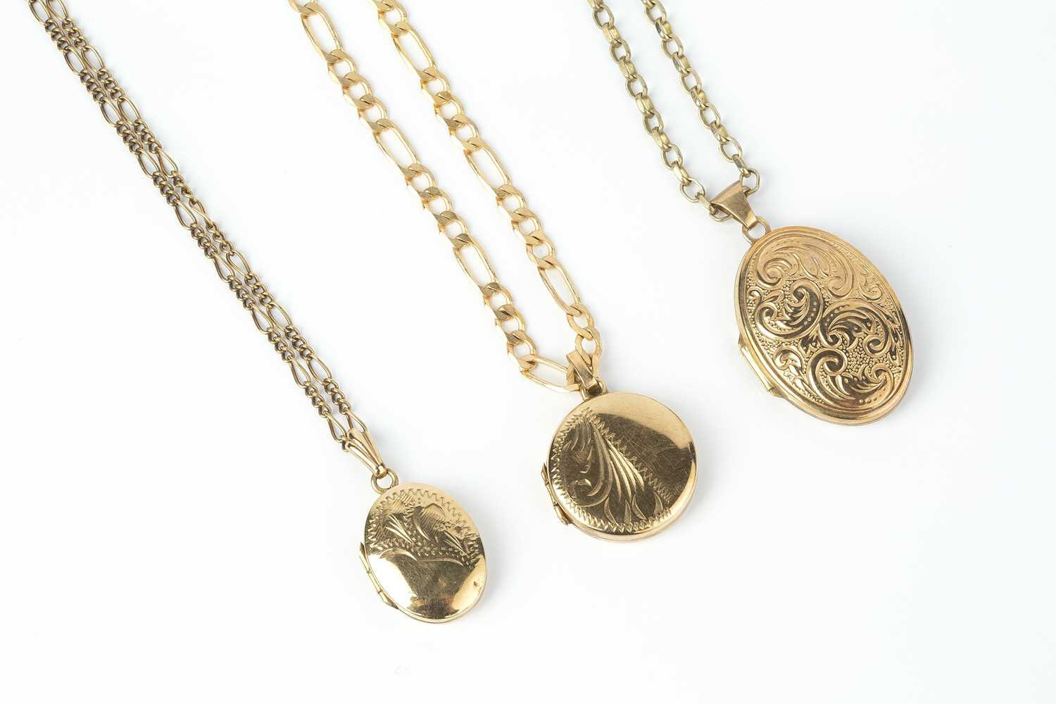 Three locket pendants on chains, comprising a 9ct gold circular locket pendant, with engraved